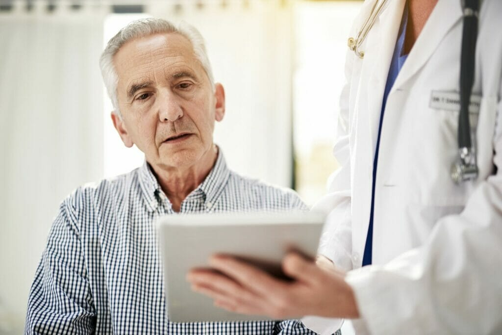 Senior with doctor reviewing information