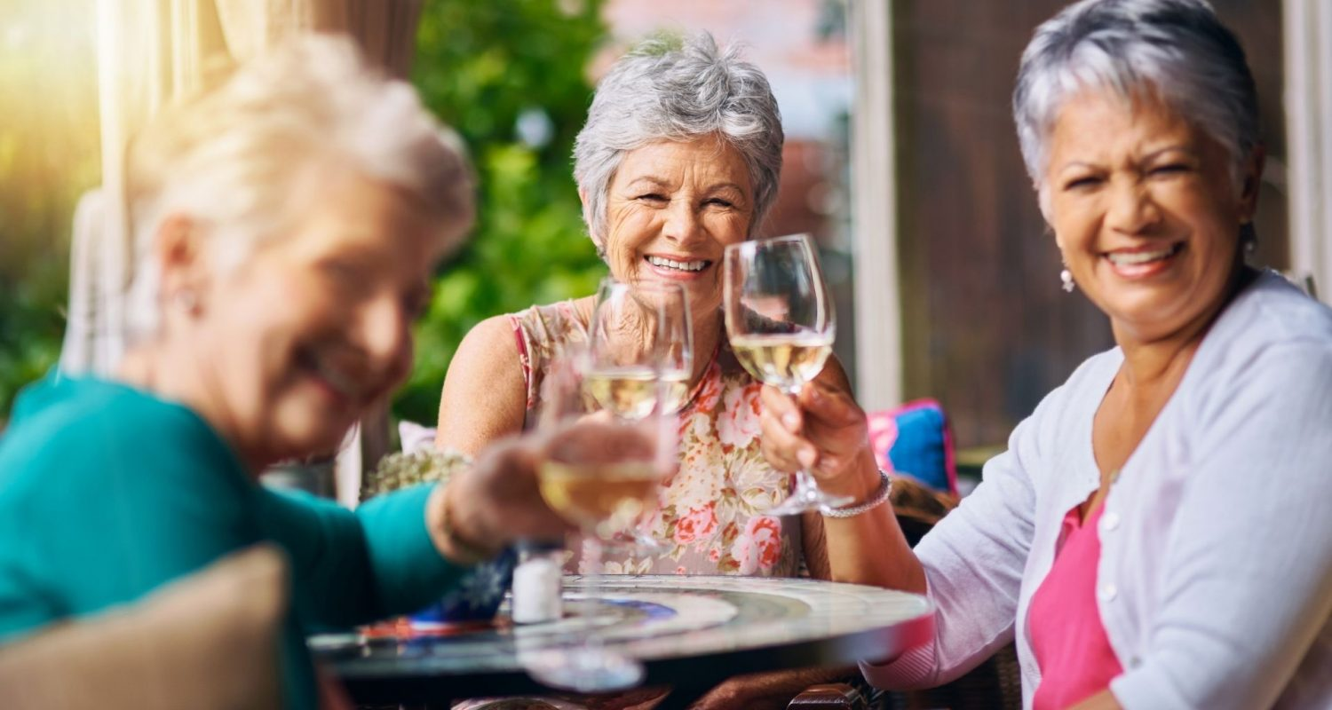 Seniors enjoying wine with friends at independent living